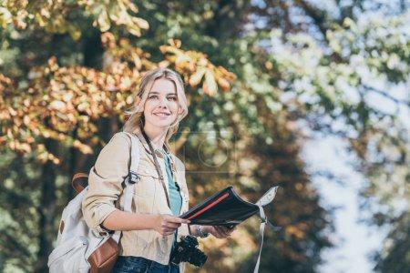Photo pour Portrait de jeune voyageur souriant avec sac à dos, appareil photo et carte dans le parc - image libre de droit