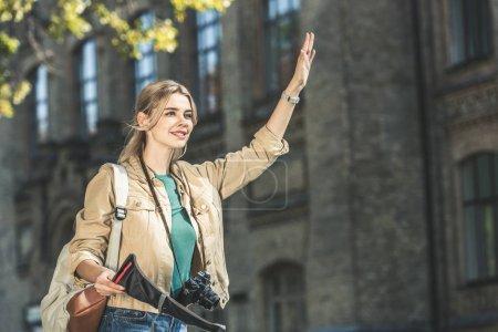 Foto de Retrato de joven viajero con mochila, cámara de fotos y mapa llamar a taxi en la calle - Imagen libre de derechos