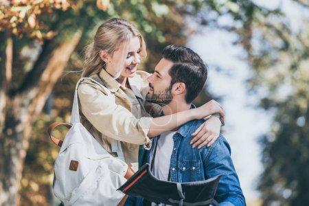 Photo pour Portrait de jeunes voyageurs avec carte câlins dans le parc d'automne - image libre de droit