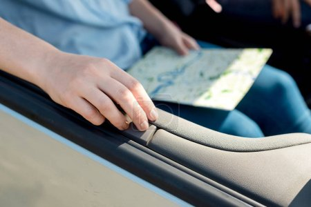 cropped shot of woman holding travel map inside car