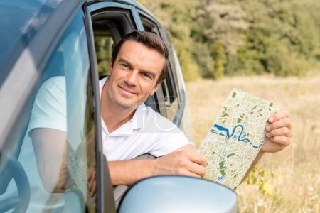 smiling man looking out car window in field and holding map