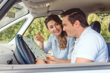 happy adult couple navigating with map during car trip