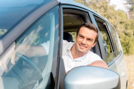 happy man looking out window while driving car in field