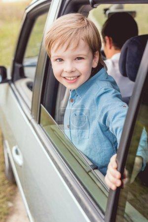 glückliches kleines Kind, das mit seinem Vater Auto fährt und in die Kamera schaut