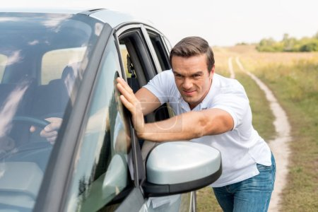 Photo pour Bel homme pousser sa voiture cassée dans le champ - image libre de droit