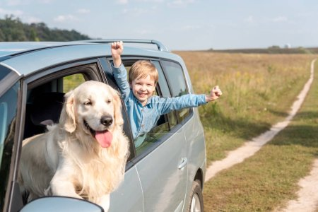 celebrating little kid riding car with his golden retriever dog in field