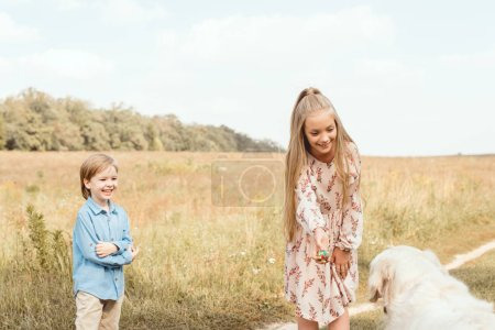 adorable little kids playing with golden retriever dog in field