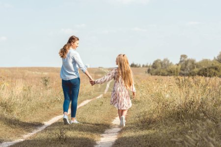 rear view of mother and daughter holding hands and walking together in field