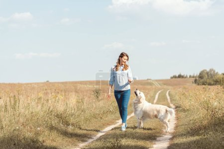 Photo for Beautiful adult woman walking by field with retriever dog - Royalty Free Image