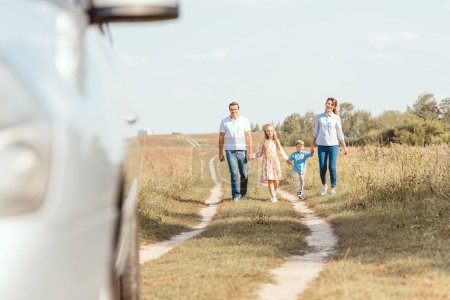 Photo for Beautiful young family holding hands and walking to car by field - Royalty Free Image