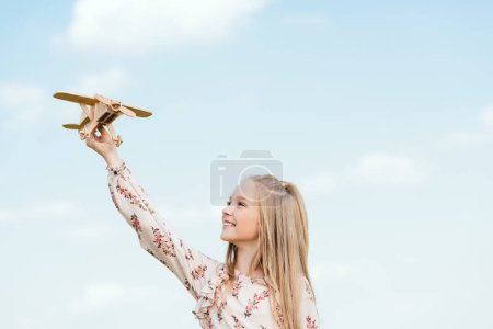 beautiful little child playing with toy airplane in front of blue sky