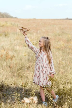 beautiful little child playing with toy airplane in field