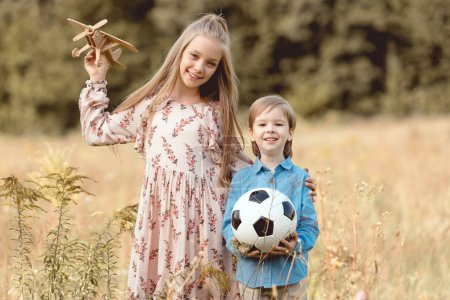 adorable little kids with toy airplane and football ball standing together in field