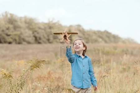happy little kid in field playing with toy airplane in field