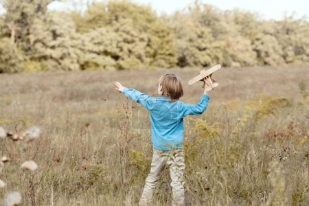 rear view of little kid in field playing with toy airplane in field