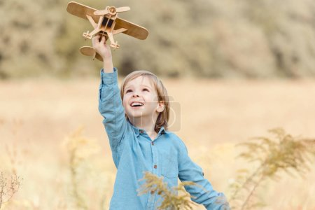 happy little kid in field playing with toy airplane in beautiful field