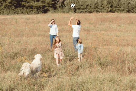 beautiful young family with retriever dog playing in field together