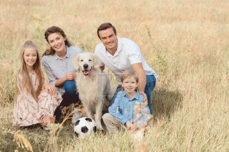 happy young family with retriever dog sitting in field together and looking at camera
