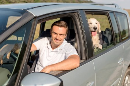 happy man with retriever dog looking out window while driving car in field