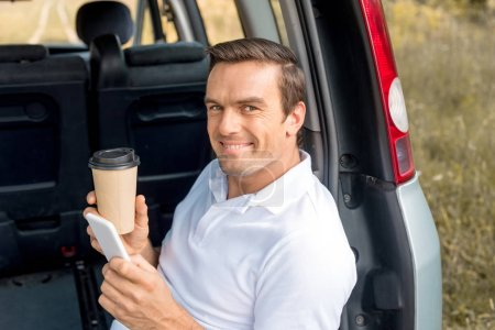 happy man with paper cup of coffee sitting in car trunk and looking at camera while using smartphone