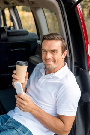 Photo for Smiling man with paper cup of coffee sitting in car trunk and looking at camera while using smartphone - Royalty Free Image