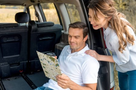 smiling adult couple looking at map while travelling by car