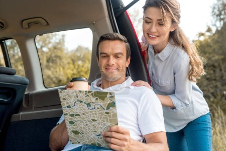 happy adult couple looking at map while travelling by car