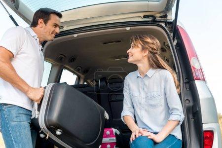 Photo pour Heureux adulte l'emballage des bagages dans le coffre de la voiture tandis que sa petite amie le regarde - image libre de droit