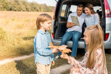 happy kids playing with toy plane while parents navigating with map and sitting in car trunk in field