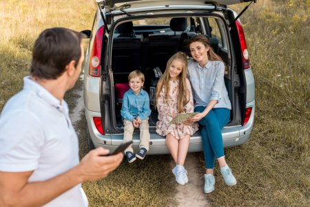 man using smartphone while his family sitting in car trunk in field