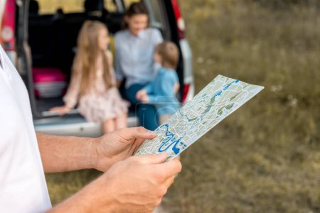 cropped shot of man holding map while his family sitting in car trunk in field