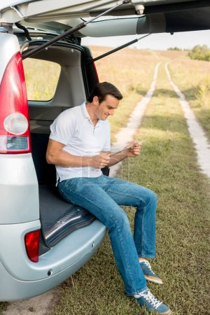 handsome smiling man sitting in car trunk and looking at map in field