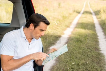 handsome man sitting in car trunk and navigating with map in field