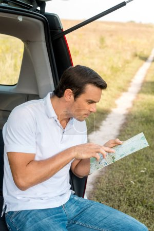 attractive man sitting in car trunk and navigating with map in field