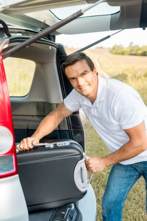 Photo for Handsome man packing suitcase into luggage boot of car in field and looking at camera - Royalty Free Image