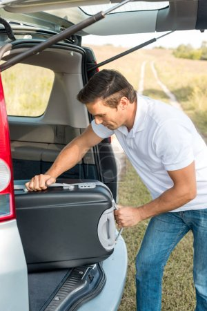 handsome man packing suitcase into luggage boot of car in field