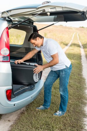 happy man packing suitcase into luggage boot of car in field