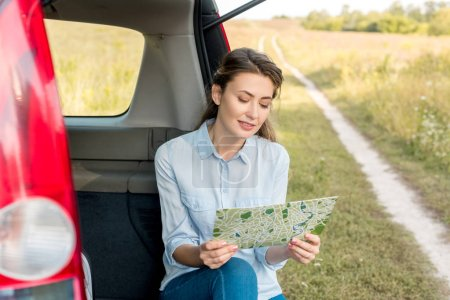 Photo for Beautiful adult woman sitting in car trunk and looking at map in field - Royalty Free Image