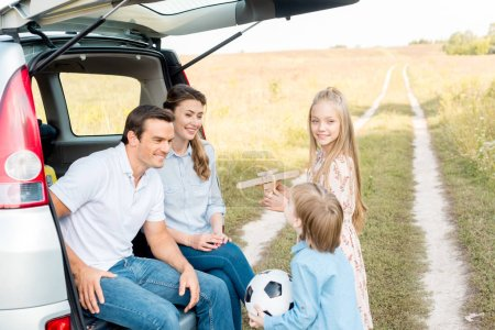 happy young family spending time together in field while having car trip