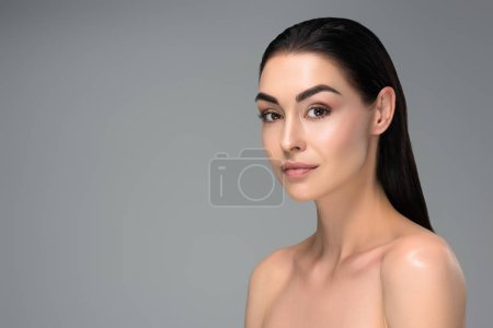 portrait of beautiful sensual naked brunette woman looking at camera isolated on grey