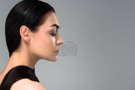 Photo pour Profil de belle jeune femme brune regardant loin isolé sur gris - image libre de droit