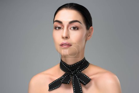 beautiful brunette woman with black bow on neck looking at camera isolated on grey