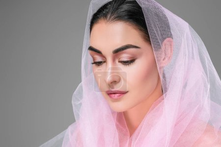 beautiful young woman with pink veil looking down isolated on grey