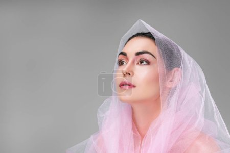 beautiful young woman with pink veil looking up isolated on grey