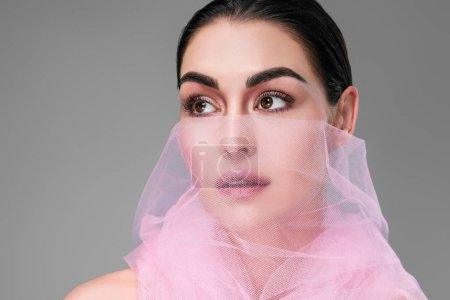 beautiful young woman with pink veil on face looking away isolated on grey