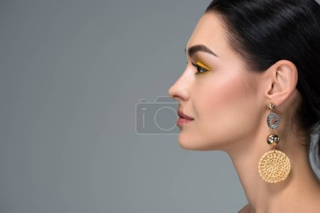 side view of young brunette woman with beautiful earring looking away isolated on grey