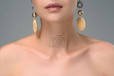 Photo pour Plan recadré de jeune femme nue avec des boucles d'oreilles élégantes isolées sur gris - image libre de droit