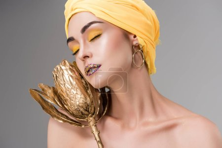 sensual naked girl in yellow turban holding golden protea flower isolated on grey