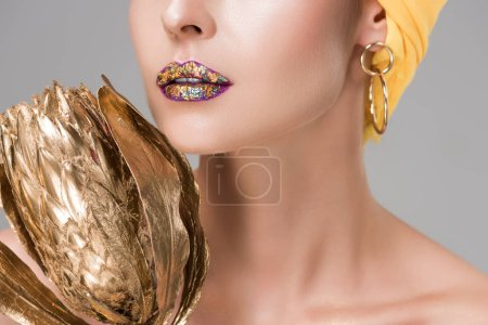 cropped shot of sensual woman with shiny lips holding golden protea flower isolated on grey