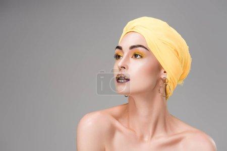 beautiful naked woman in yellow turban looking away isolated on grey